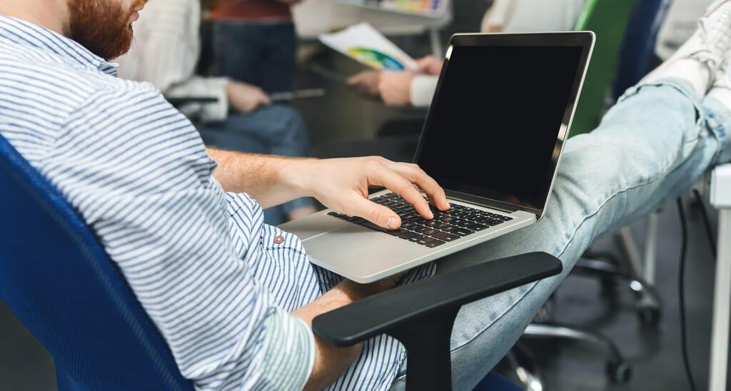 Emprendedor trabajando en laptop con pantalla en blanco